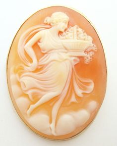 Antique 14K yellow gold cameo pin featuring an oval shell cameo that has a figural of a woman and basket set in the center.  Dates between the 1900-1920's.