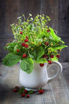 Bouquet of wild strawberries in a white pitcher