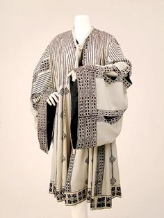Fortuny Black and Ivory Silk Coat Italian, 1930s  The ivory background printed with motifs inspired by Coptic and Islamic art, very wide sleeves, Venetian glass bead trim at front and along slits in skirt and sleeves, long ivory rouleau tie closure at neck with self tassels, black silk lining, silk faille label: Mariano Fortuny/Venice.  Very good condition, minor discolorations, appears to have been shortened.