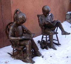 Cute bronze statues of a young boy and girl reading outside in the snow!