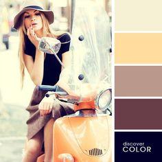 Chica en una motocicleta usando una falda de color café con una blusa negra y un sombrero de color café
