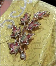 """The Enamel Maple Leaves Brooch is a corsage of six maple leaves made from blended colors of enamel from green to pink. The leaves are tipped in diamonds and their stems come together to end with a single pearl in a diamond setting. Queen Mary received an """"enamel maple leaf spray"""" while on a tour of the Realm in 1901. This may have been unseen until the Queen brought it out during her 2010 Canadian tour, so if it is in fact Queen Mary's, it may have had a particularly long nap in the vaults."""