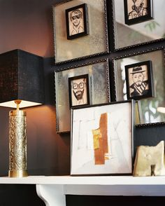 - A grouping of art with a gold lamp on a white shelf