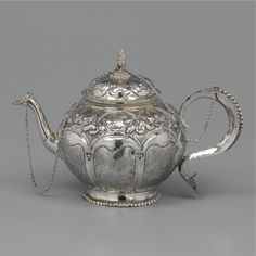 A DUTCH SILVER TEAPOT, PROBABLY JAN DE VRIES, AMSTERDAM, 1725 vase-shaped, on circular beaded foot, chased with eight matted panels, cover with shells and repeated foliate design, with pineapple-shaped finial, the cover connected with two silver chains to the spout and beaded handle, marked below 269gr., height 13.8cm.