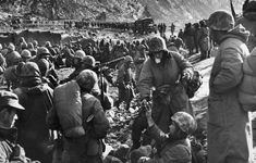 Marines rest after making it through the canyon road known as Nightmare Alley during the retreat from the Chosin Reservoir, December 1950.