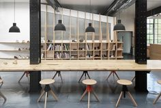 Paris-based ARRO Studio has transformed a 19th-century warehouse into the design studio for British shoe brand Clarks, adding factory-shaped volumes that house meeting rooms and offices.