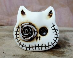 Skull cat in white with a dirty rose in his eye. Brooch, keychain, pendant or magnet (you choose)