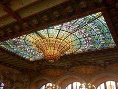 Esta ventana de vitral está en el techo del Palau y es increíble. Es muy única porque la locación es diferente y es muy intricada porque es de muchos trozos pequeños de colores ricos. La ventana es el elemento principal del espacio y hace pasar mucho luz. La forma de la ventana es muy única también aparece como un candelabro.