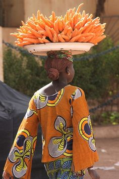 Lady carrying carrots on her head in Mali, Africa