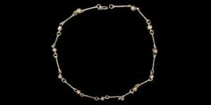 """9th-11th century AD. A necklace formed from twisted wire shanks with a loop to each end alternating with wire-mounted pierced oblate shaped drawn glass or crystal beads; hook clasp. 22 grams, 50 cm (19 3/4"""")."""