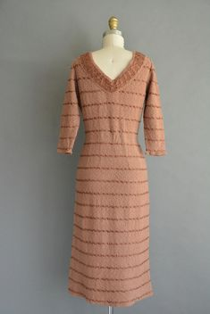 Gorgeous vintage 1950s brown soft knit wiggle dress with ribbon detail throughout, v neckline with bust darts and a nipped waist fit, stretch fitting. ✂------ M E A S U R E M E N T S ------- best fit: medium / large bust: 38-40 waist: 28-30 hips: up to 42 total length: 44