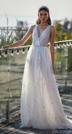 Sparkly vintage a-line wedding dress with v-neckline, wrap bodice and shimmery fabric | Bridal gown with feather appliques and belt | Ida Torez Wedding Dresses 2021 Brave Glanze Collection - 01224- Absorbing beauty - Belle The Magazine | See more gorgeous bridal gowns by clicking on the photo