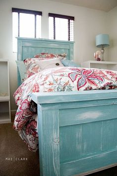 Shabby chic, white-washed aqua bed is perfectly matched with the colorful bedspread
