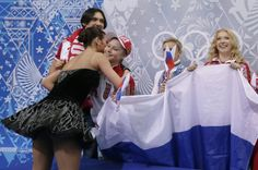 Elena Ilinykh, left, embraces Julia Lipnitskaia of Russia, second from left, after she and Nikita Katsalapov of Russia competed in the team ...