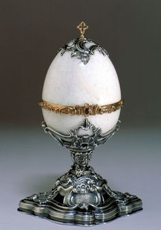 The Rosebud egg is a jewelled enameled Easter egg made by Michael Perchin under the supervision of the Russian jeweller Peter Carl Fabergé in 1895. The egg opens like a bonbonnière to reveal a yellow-enamelled rosebud, in which the two surprises were originally contained. The surprises are missing, but they were a golden crown, with diamonds and rubies, and cabochon ruby pendant.