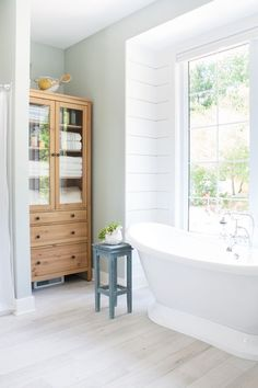 Lake house master bathroom featuring Blustery Sky blue cabinets, white shiplap, and warm wood tones. A pedestal tub and chrome accents complete the look. Bad Inspiration, Bathroom Inspiration, Pedestal Tub, White Shiplap, Rustic Home Interiors, Blue Cabinets, Glass Cabinets, Wood Cabinets, Bathroom Interior Design
