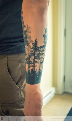 Trees are perfect subjects for tree tattoos, as shown in this example. The artist uses various shades of black and gray to create pine trees of various heights around the whole arm. The start from a dark band of underbrush around the wrist and reach to the elbow.
