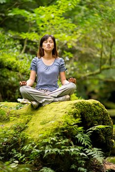 Young woman doing yoga meditation on old tree trunk in deep forest     LEARN HOW TO STAY IN SHAPE THIS HOLIDAY SEASON    http://elitegreatness.com/blog/2012/11/26/learn-how-to-enjoy-this-holiday-season-while-still-losing-fat/