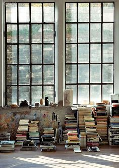 Windows, stacks of books, magazines, records, paint on the wall, cement, light, mood, interior