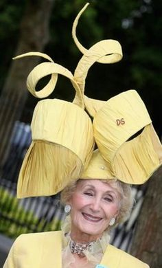 Florence Claridge has been attending Ascot for 25 years, and each year her hats are stunning in every sense of the word. If you notice the DS on this year's yellow hat, it stands for David Shilling, who many consider to be the finest milliner in the world.  His sculptural and architectural hats are one of a kind works of arts, appearing in museums around the world.