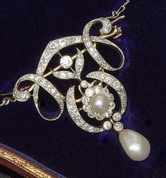 A late 19th century pearl and diamond brooch/pendant.  Of scrolling openwork cartouche design, centrally set with a half pearl and old-cut diamond cluster, bordered by channels of single and old-cut diamonds, suspending a diamond and pear-shaped pearl drop below, with detachable brooch fitting, on a fine figaro-link chain, in fitted case signed 'Winsor Bishop, Norwich'