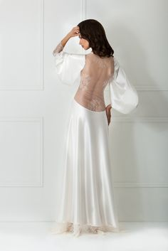 This royal white robe by Amoralle exudes cinematic glamour. Complemented with vintage-inspired exquisite lace trim and back, the full sleeve robe does not get much more luxurious than this. Decorated with feminine closing ribbons, this deep décolleté slim Satin Gown, Satin Dresses, Gowns, Luxury Nightwear, White Lilly, Night Gown, Lace Trim, Vintage Inspired, Ballet Skirt