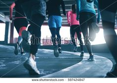 Back view of young sportspeople running on race track at sports ground.