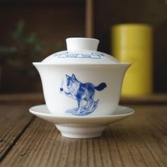 A handy teaware can be served as a profound blessing to loved one. Wolf Tea Relaxing Kungfu Gaiwan — a piece made from porcelain, decorated with a modern painting of a smiley wolf surfing with tea leaves!    #teawares #gaiwan #kungfutea #wolf #teaset