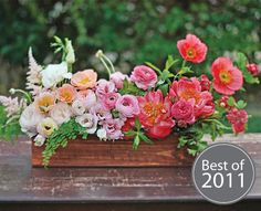 Striking centerpiece, by Honey and Poppies, features garden roses, poppies, lisianthuses, ranunculuses, and peonies