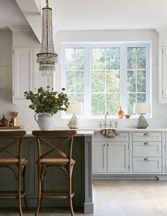 Vintage modern kitchen in white and gray with an antique crystal chandelier over the island and antique style bistro chairs - Kitchen Ideas & Decor