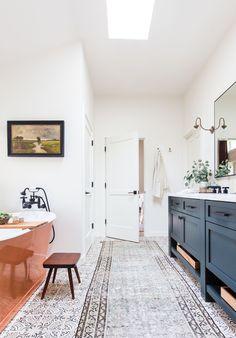 copper bathtub blue cabinets black fixtures