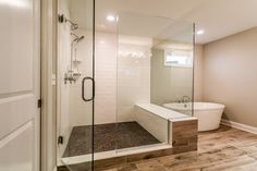 Luxurious Oversized Master Shower with wood like tile detail and white subway tile