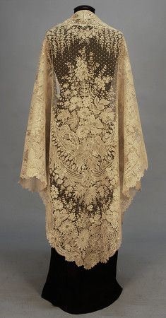 Handmade Brussels Applique Lace Shawl, mid. 19th century -- Large cotton net triangle lavishly decorated with Point de Gaz and bobbin lace in a pattern of wisteria, hydrangea, lilac and other blossoms amid swags, ribbons and foliage. excellent. $1500-$2,500.