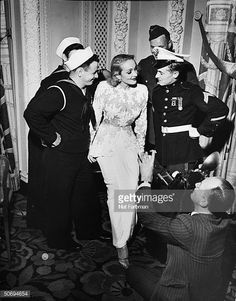 Actress Marlene Dietrich surrounded by two sailors a soldier a Marine as new photographer Ray Howard hones in w his Speed Graphic camera at USO in...