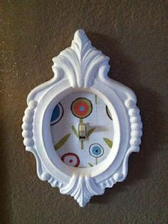 This idea is simple & cute: Use a frame & some nice paper to make a boring light-switch something great!