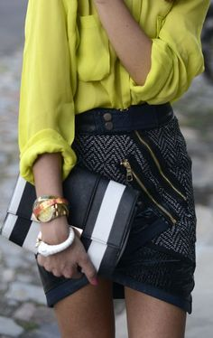 Asymmetrical black patterned skirt with yellow blouse and black and white clutch