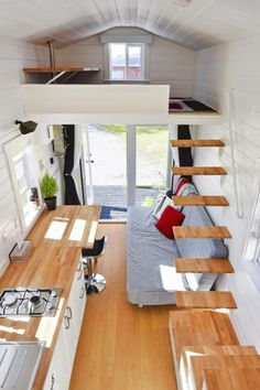 This loft is accessed by floating stairs.  Below you can see the kitchen, desk, and couch.