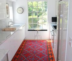 the kitchen doesn't have to attract the eye, alternatively the floor can! interesting idea (love the colours)