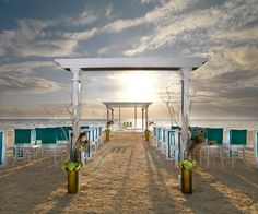 Exotic Peacock. Chair backs adorned with squares of brilliant turquoise and crisp white merge perfectly with floral hues of green, while iridescent peacock feathers add multidimensional accents and inspiration. The freestanding white wedding gazebo pops against the sparkling blue waters.