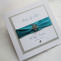 Handmade wedding invitation featuring antiqued silver centrepiece mounted on teal satin ribbons