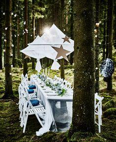 Jedálenská zostava na svadbu v prírode s dlhým bielym stolom, bielymi skladacími stoličkami, závesnými dekoráciami a svetelnými reťazami na stromoch
