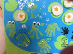 Hand print frogs on life cycle pond.