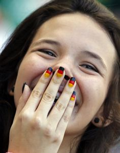 A German soccer team supporter with her nails painted in her national colors smiles before the group G World Cup soccer match between Germany and Portugal at the Arena Fonte Nova in Salvador, Brazil, Monday, June 16, 2014. (AP Photo/Matthias Schrader)