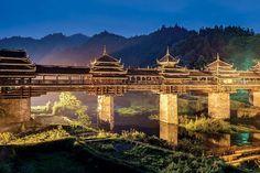 Ponte Chengyang, China. Localizada em Sanjiang, região habitada pela etnia Dong, a ponte tem o estilo de arquitetura desse povo, acostumado a construir travessias cobertas. Inaugurada em 1916 sobre o Rio Linxi, ela é feita de madeiras e pedras, sem o uso de pregos ou rebites. Também chamada de Chengyang Vento e Chuva, a ponte proporciona uma vista pitoresca aos pedestres que a atravessam: camponeses trabalhando nos arredores e árvores do chá no topo das montanhas.  Fotografia: Getty Images.