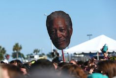A giant Morgan Freeman head floats above the #HangoutFest crowd as The 1975 play