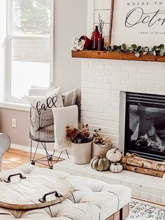 Decorating a neutral farmhouse fall fireplace hearth and mantle with a combination of faux florals in vintage crocks, green faux pumpkins, a large fall farmhouse sign, and neutral and earth tones create this cozy fall fireplace. Terracotta pots and vintage amber bottles, birch logs, cream throws and linen pillows create a cozy space by the fire. - Rain and Pine #farmhousedecor #falldecor #fallfarmhousedecor #fallcottagedecor #cottagedecor #fallcottagedecor #neutraldecor #cozydecor