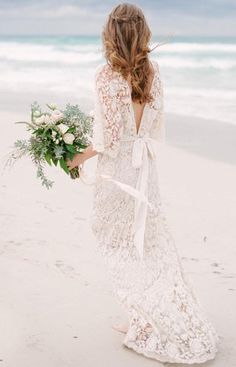 Spring Roses Wedding Gown by Kite and Butterfly ---Get swept away in this ornate French lace gown that was inspired by the 60's. Finished off with long bell sleeves, plunging neckline, low v back, and dramatic train, this dress is perfect for the free-spirited bride.