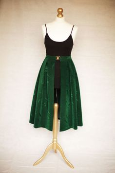 A SKIRTTAIL is a unique, handmade decorative over-skirt that can be worn over the top of any dress or any skirt/top combination that you already have on. It is worn high on the waist and fastened neatly with a gold clasp. The gap in the centre of the fabric elegantly reveals the garment that you have on underneath, instantly updating your outfit. Emerald green Mid-length available on Etsy.