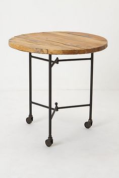 """Anthropologie                                     DETAILS                  Form meets function on this handcrafted piece, composed of a smooth wood top and wheeled iron legs so you can move it from couchside to bedside with ease.  Antique black and natural wood finish Iron, wood 25.5""""H, 23"""" diameter Imported"""
