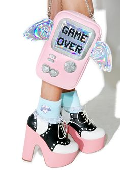 """Skinnydip Game Over Cross Body Bag will have 'em hatin' tha playa cuz you look so damn kyoot! This gamer cross body purse is in the shape of our favorite handheld electronic toy with iridescent angel wings for moral support. With """"GAME OVER"""" printed on its screen, this bb is complete with a zip top closure and removable chain strap, so you'll always be ready to try to beat yer last high score."""